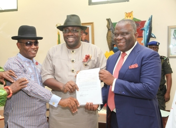Bayelsa State Governor, Hon. Seriake Dickson (centre) supported by his Deputy, Rear Admiral Gboribiogha John Jonah (Rtd) (left) handing over a draft donation for the sum of N500m from Dr. Mike Adenuga to the Chairman of the newly inaugurated Flood Committee, Gen. Andrew Owoye Azazi (Rtd) at Government House in YenagoaPhoto by Lucky Francis, Government House, Yenagoa