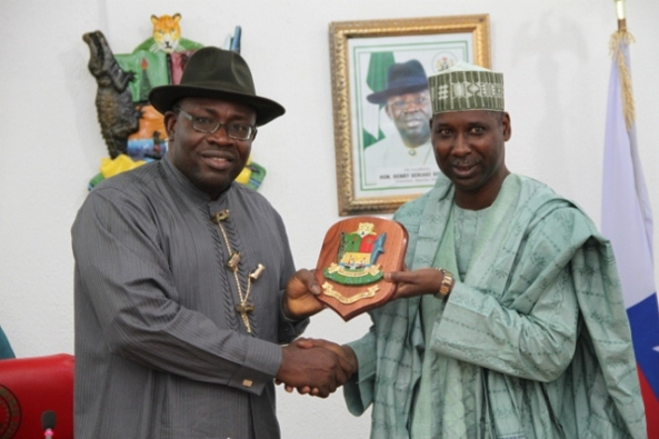 Bayelsa State Governor, Hon. Seriake Dickson (left) makes a symbolic presentation the State's Coat of Arms to the visiting Director General of the National Institute for Policy and Strategic Studies, Kuru, Prof. Tijjani Mohammed-Bande, during a courtesy call on the Governor by members of Senior Executive Course No.35,2013, of the National Institute, at the Government House,  Yenagoa.